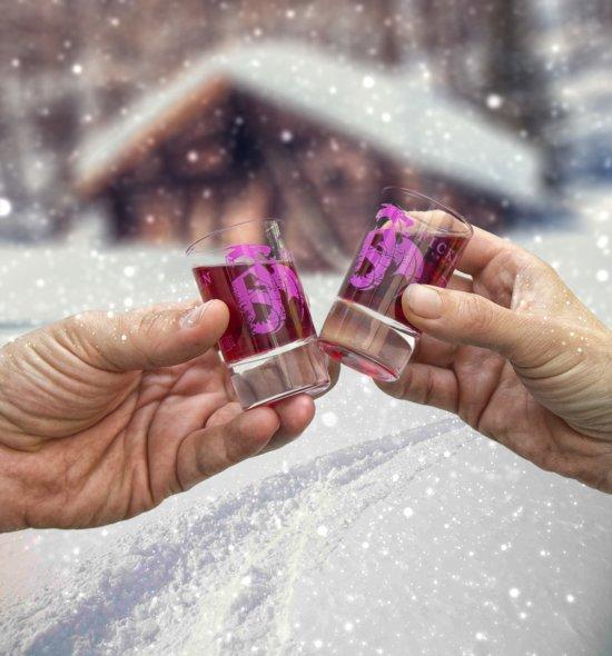 Anstoßen im Schnee mit Schnapsgläser